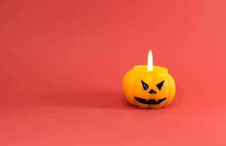 One scary orange pumpkin shaped candle with a fire, isolated on red background, space for text. Tradition Happy Halloween concept.