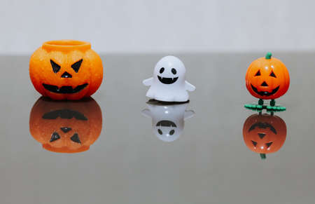 One scary orange pumpkin shaped candle, plastic white ghost toy and orange funny smiling pumpkin toy with green legs, isolated on gray background, space for text. Tradition Happy Halloween decoration.