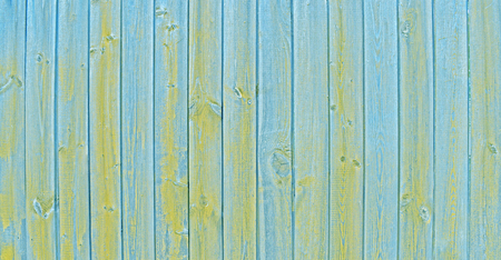 Natural wooden background. Surface of wooden texture for design and decoration. Shabby vertical boards with peeling paint. Blue and yellow color. Copy space.