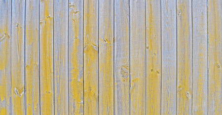 Natural wooden background. Surface of wooden texture for design and decoration. Shabby vertical boards with peeling paint. Gray and yellow color. Copy space. Фото со стока