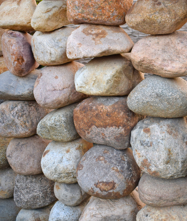 Garden fence of large natural round stones. Cobblestone wall. Background.