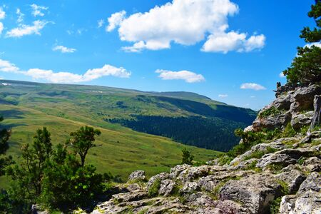 Picturesque mountains, meadows, green pines on the cliff side. Blue sky and white clouds. Summer landscape, sunny day. Horizontal photo. Lago-Naki Plateau, Adygea.