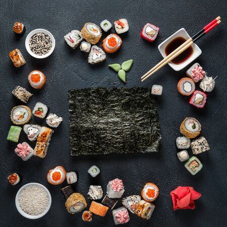 A set of traditional Japanese dishes on a dark background. Sushi rolls, nigiri, rice, pickled ginger. Frame made of Asian cuisine.