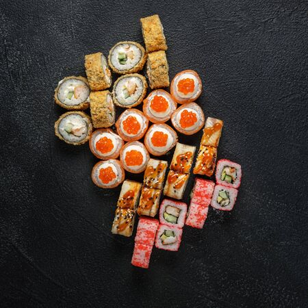 Set of traditional japanese food on a dark background. Sushi rolls, nigiri, raw salmon steak, rice, cream cheese, avocado, lime, pickled ginger. Asian food frame. Dinner party. Stock Photo