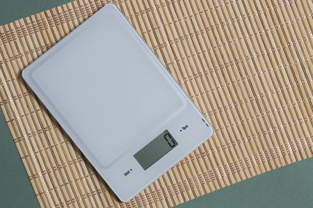 Empty kitchen scale on bamboo mat and green paper background. Reklamní fotografie - 79299671