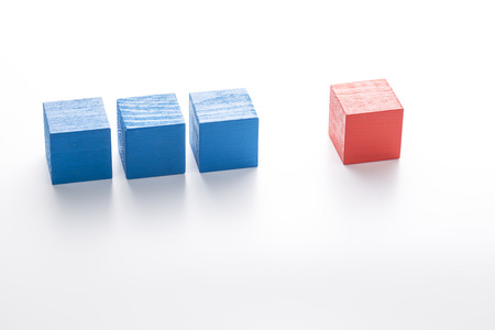 differentiation: Three blue wooden cubes and red one. Individuality concept. Stock Photo
