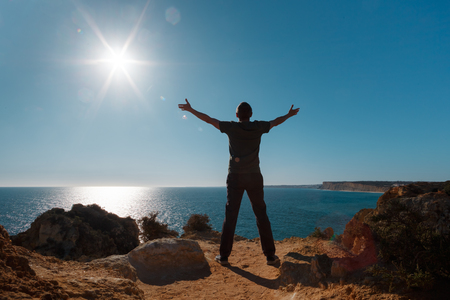 Arms raised man standing on the cliff in front of Atlantic ocean. 스톡 콘텐츠