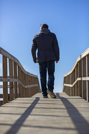 Rear view of a man walking away on wooden boardwalk. Stock Photo