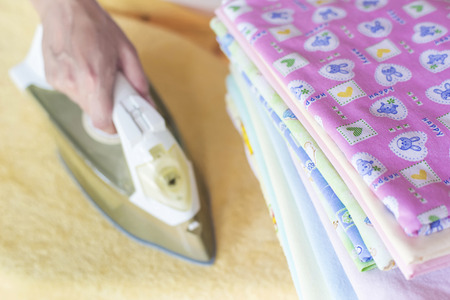 Woman ironing clothes on the ironing board photo
