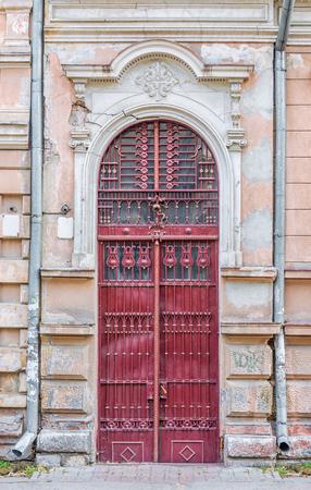 puertas de hierro: antigua puerta de color rojo con detalles de hierro forjado en Ivano-Frankivsk, Ucrania Foto de archivo