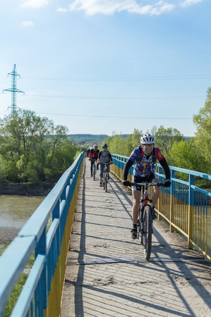 pedestrian bridge: Ivano-Frankivsk, Ukraine - May 3, 2015: tourists on bicycles riding through a pedestrian bridge over the river Bistrica. Bridge railing painted in colors of Ukrainian flag.