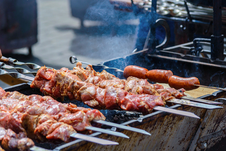 coals: cooking meat and sausages on skewers, shashlik on coals Stock Photo