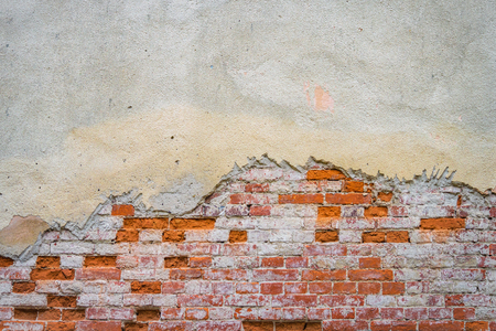 Grunge brick wall of the old house. Textured background. Remains of old plaster Stock Photo