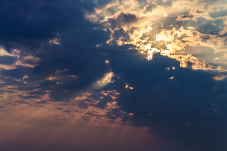 rays of the sun make their way through dramatic clouds Stok Fotoğraf