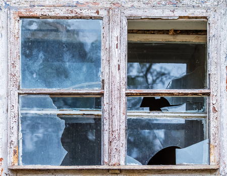 The old window of an abandoned house with shabby paint and dirty, broken glass