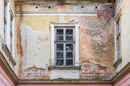 background texture of an old brick wall with window and remains of multi-colored plaster