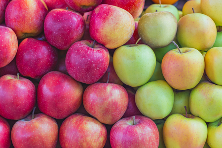 background texture of multi-colored apples stacked on the market counter