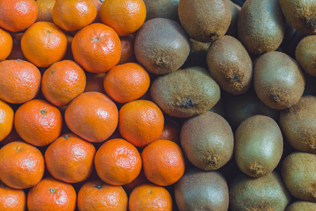 background texture of folded kiwi fruits and tangerines on the market counter Stok Fotoğraf