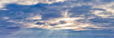 background panorama. rays of the sun make their way through dramatic clouds Stok Fotoğraf