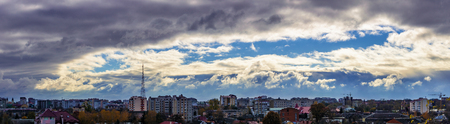 rays of the sun make their way through dramatic clouds, located by a ring, over the city of Ivano-Frankivsk, Ukraine