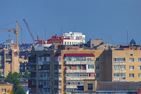 City landscape. Old multi-storey houses and modern buildings against the blue sky. Roofs of apartment buildings.