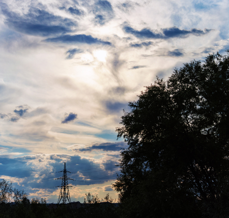 silhouettes of trees and a high-voltage tower against the background of dramatic clouds, through which the rays of the sun make their way
