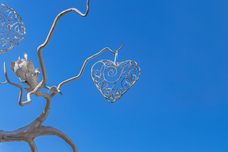 stylized filigree heart hanging on the tree of forged metal with flower on blue sky background
