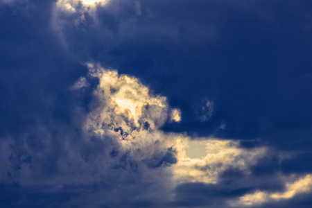 Thunderstorm sky background, rays of the sun make their way through dramatic clouds Stok Fotoğraf
