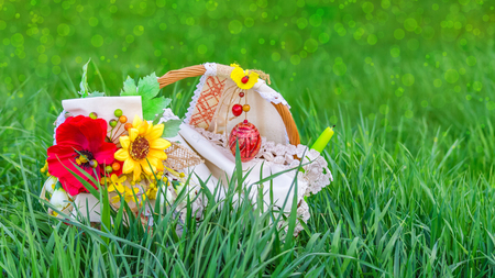Easter basket in green grass, on a blurred background of meadow with bokeh effect Stok Fotoğraf