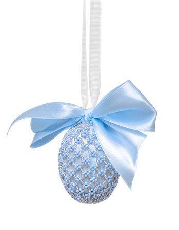 Easter egg decorated with beads and a bow in blue hues, hanging on a white background