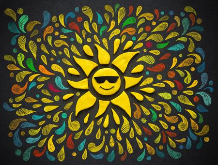 alegria: sol de la felicidad en el fondo negro. ilustración de plastilina. Foto de archivo