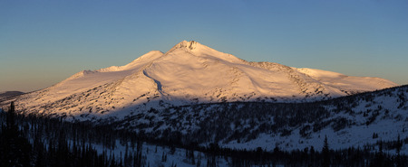 Winter mountain landscape with sunlight. Panoramic photo.