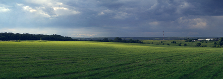 Rural panoramic landscape with sun-lit field, before a thunder-storm. Stock fotó - 104923130