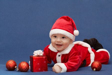 baby in santas suit with gift and christmas balls photo