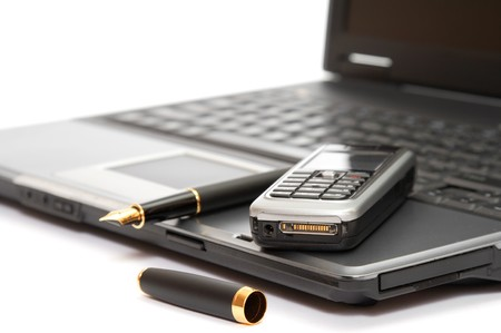 mobile phone and fountain pen on the laptop photo