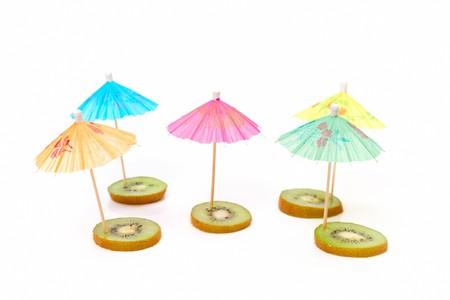 cocktail umbrellas on the slices of kiwi photo