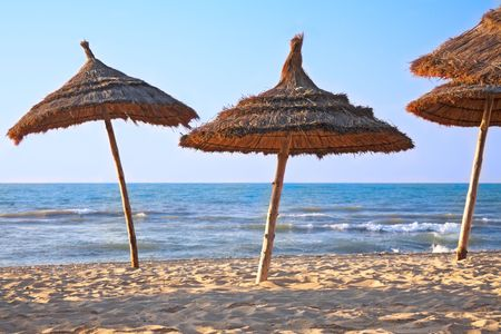 sunshades: thatched sunshades on the beach Stock Photo