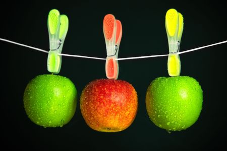 three apples with clothespins in a row on black background photo