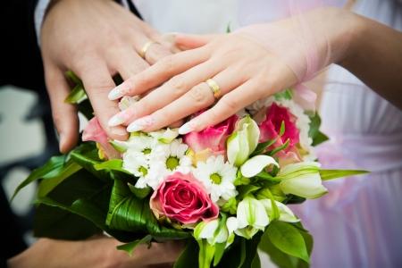 ceremonia: manos de recién casados con bouquet de boda Foto de archivo