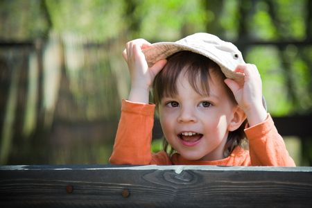 playful child holding his hat photo
