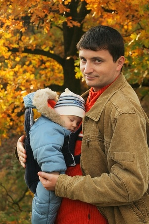father holding his son in baby carrier photo