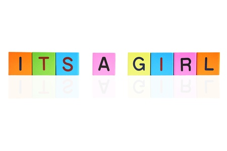letter blocks: phrase ITS A GIRL formed with wooden letter blocks