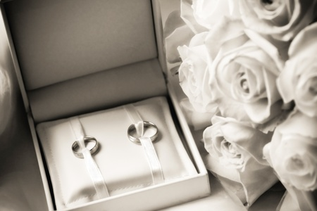 wedding rings in a box with bouquet photo