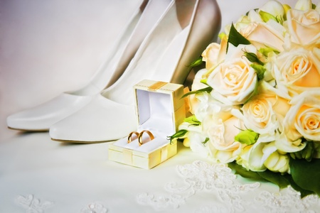 wedding rings in a box with bouquet and high heel shoes Stock Photo