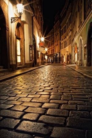 callejón estrecho con linternas en Praga en la noche