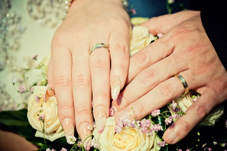 hands of bride and groom with wedding bouquet photo