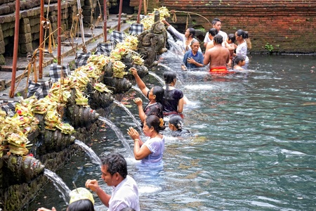 TAMPAK SIRING, BALI, INDONESIA - OCTOBER 30: People praying at holy spring water temple Puru Tirtha Empul during purification ceremony on October 30, 2011 in Tampak Siring, Bali, Indonesia Publikacyjne
