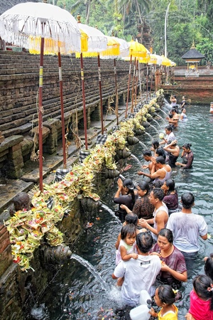 TAMPAK SIRING, BALI, INDONESIA - OCTOBER 30: People praying at holy spring water temple Puru Tirtha Empul during purification ceremony on October 30, 2011 in Tampak Siring, Bali, Indonesia