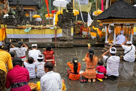 TAMPAK SIRING, BALI, INDONESIA - OCTOBER 30: People praying at holy spring water temple Puru Tirtha Empul during the religious ceremony on October 30, 2011 in Tampak Siring, Bali, Indonesia