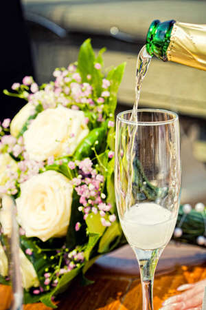glass of champagne with wedding bouquet photo